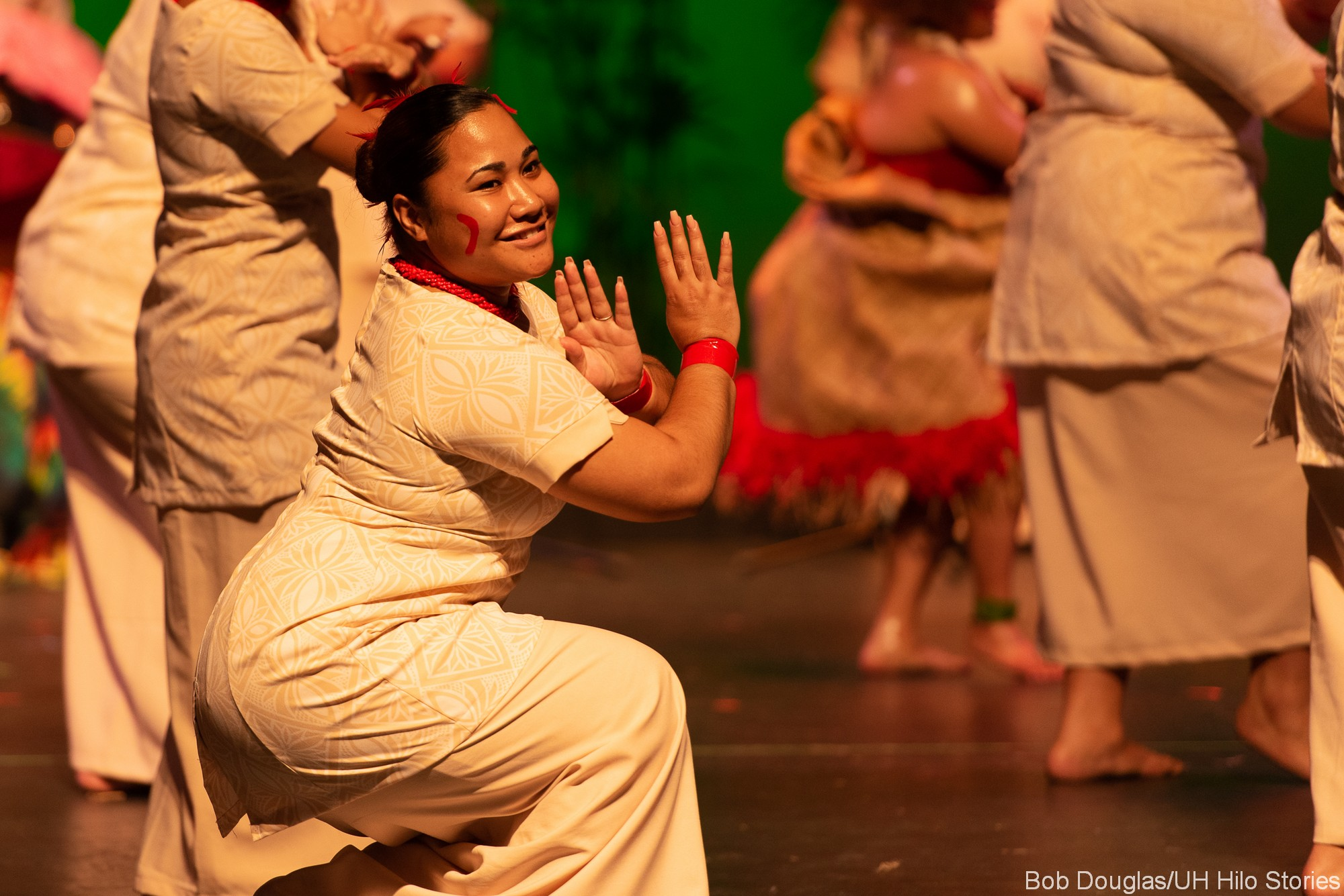 Single woman dancer dancing, crouched down, smile, graceful hands.