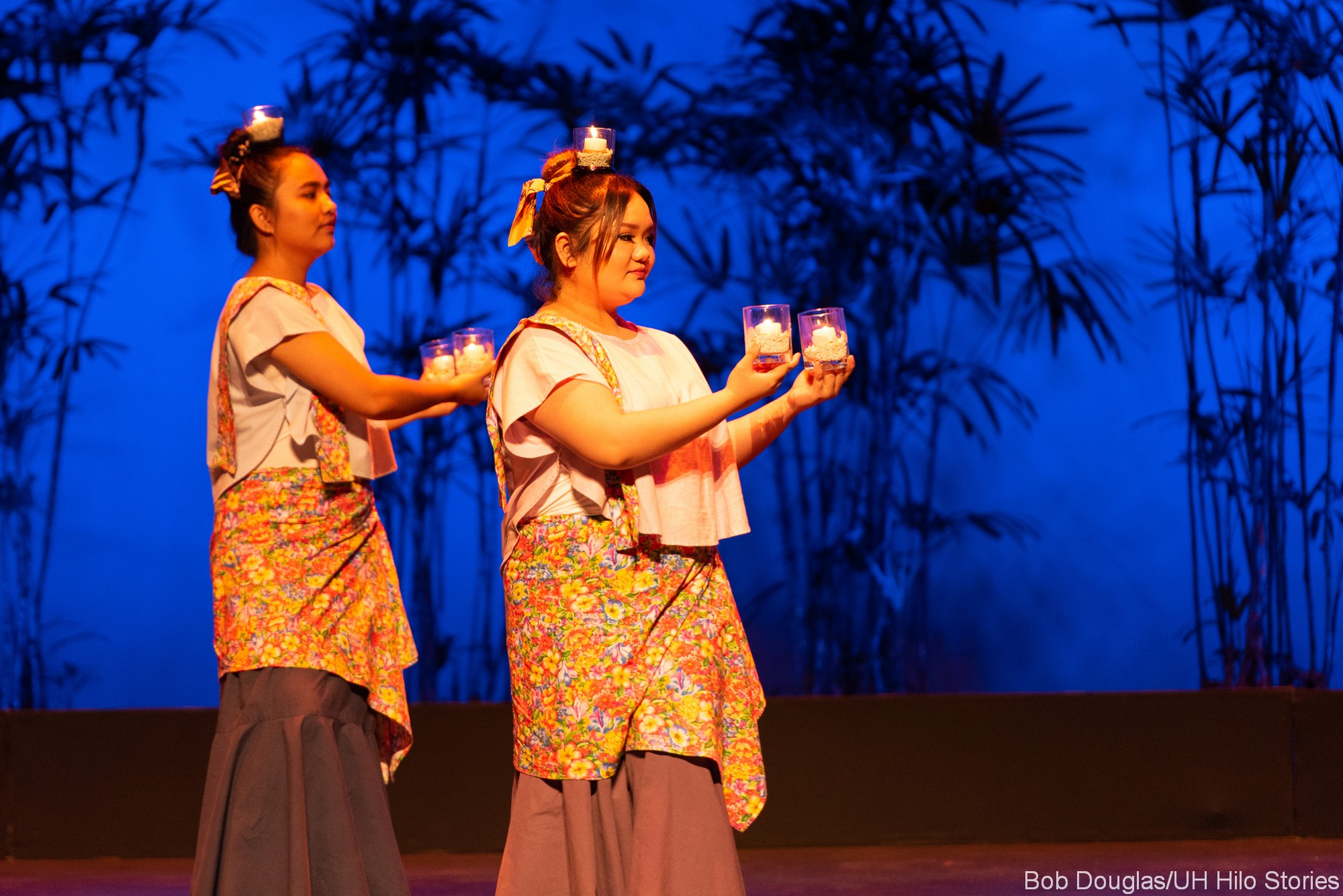 Two women doing traditional Philippine folk dance with candles.