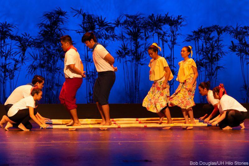 Dancers doing Tinikling traditional Philippine folk dance