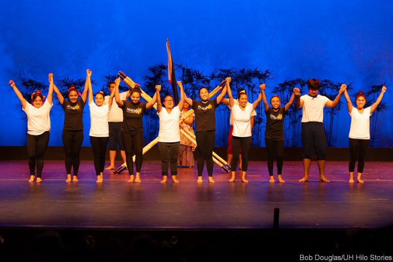 Dancers grouped together holding hands and jumping for joy.