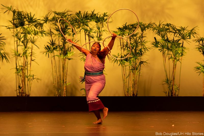 Woman dancing holding large hoops overhead.