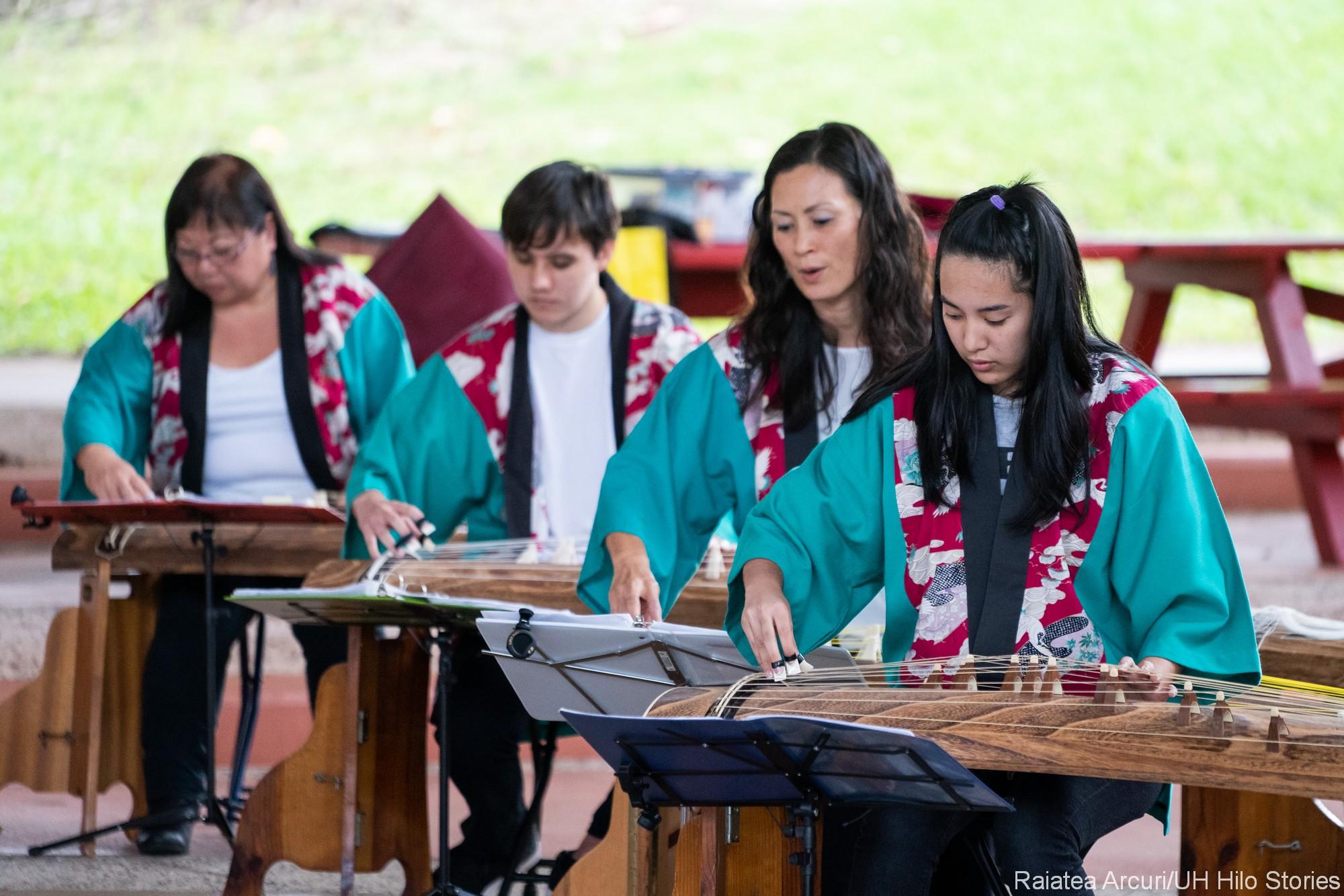 Four women playing koto.