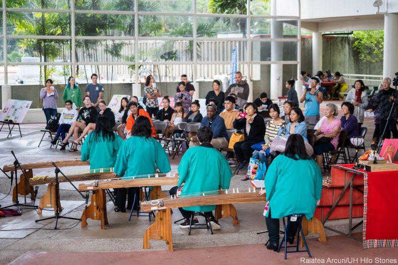 Audience watching four women playing koto harps.