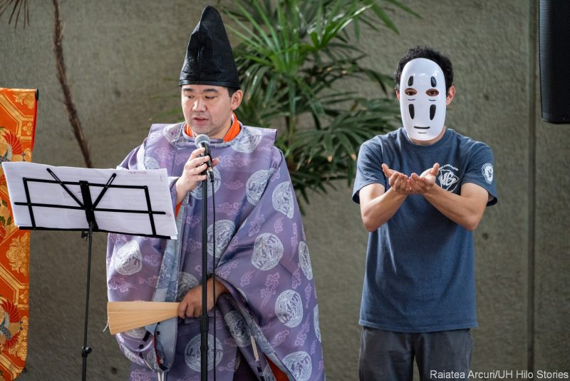 Hatted and masked Japanese performers in costume and mask.