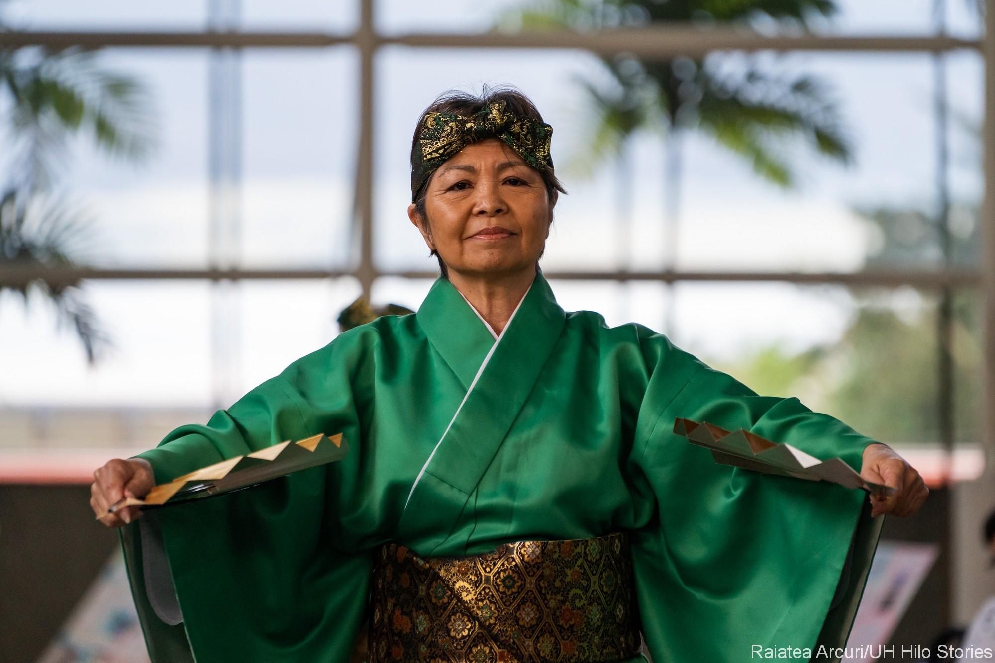 Woman in green doing Okinawan Dance.