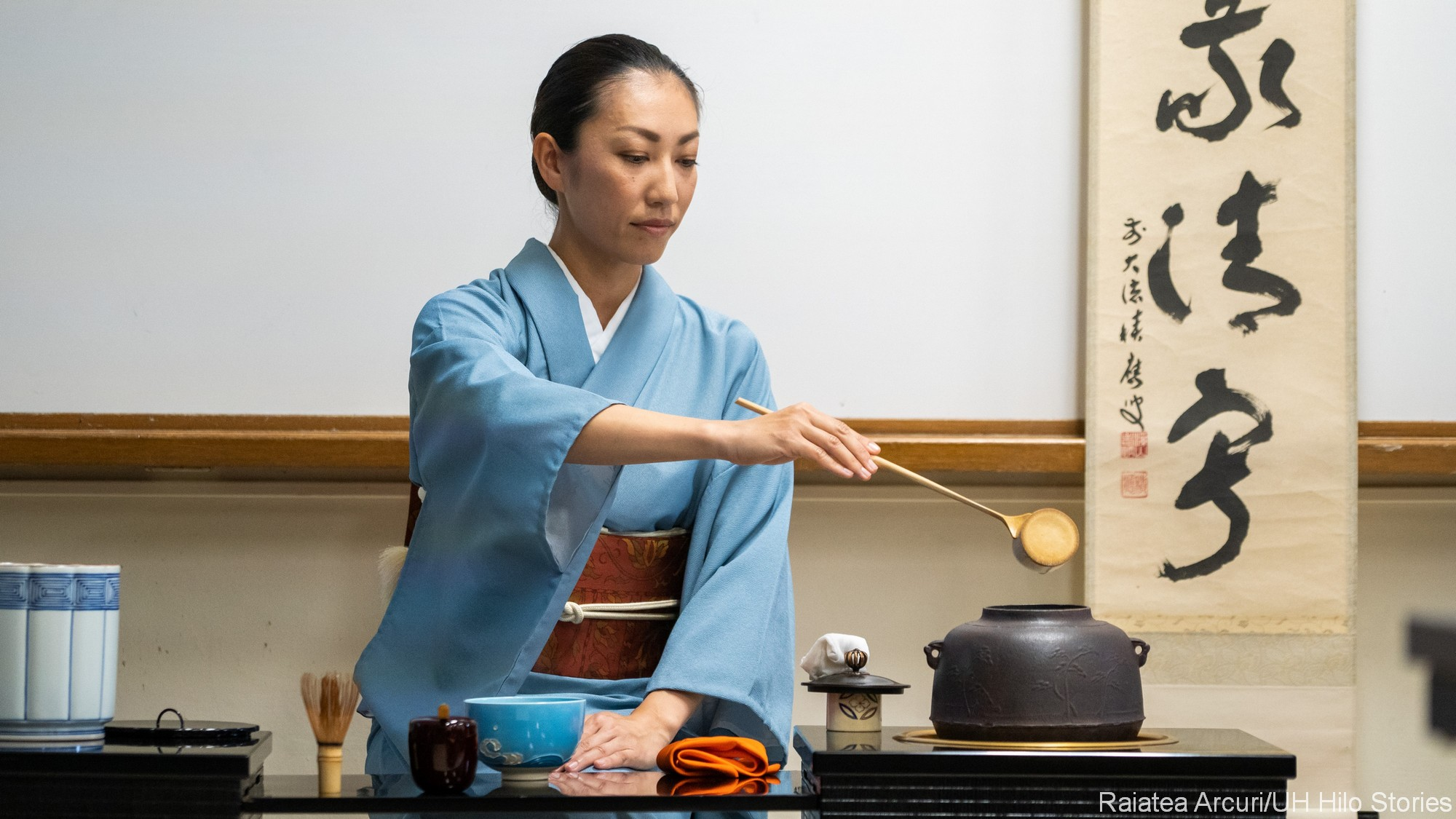 Woman in blue kimono performing tea ceremony.