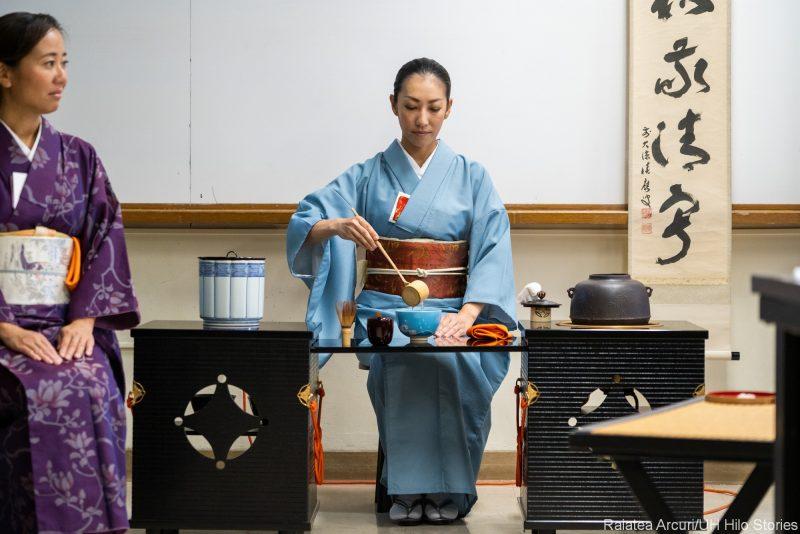 Woman in kimono performs tea ceremony.