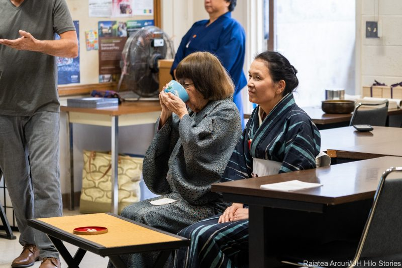 Woman drinks from ceremonial tea cup.