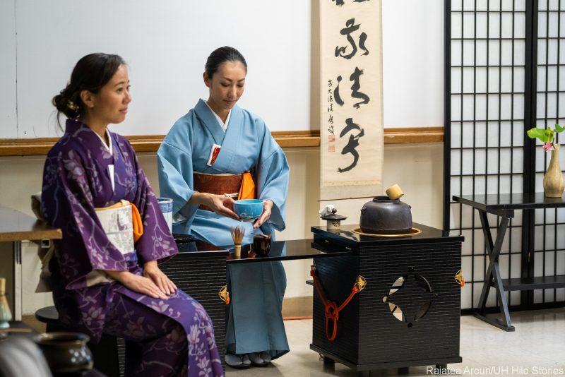 Two women perform tea ceremony.
