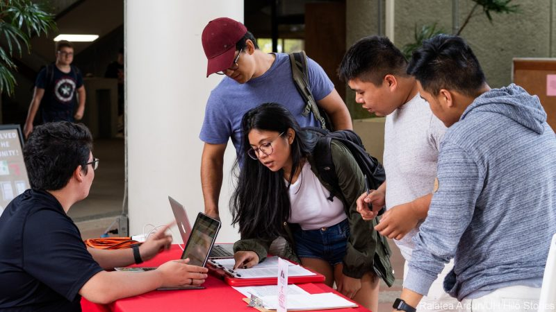 Several students stand at an informational table reviewing documents.