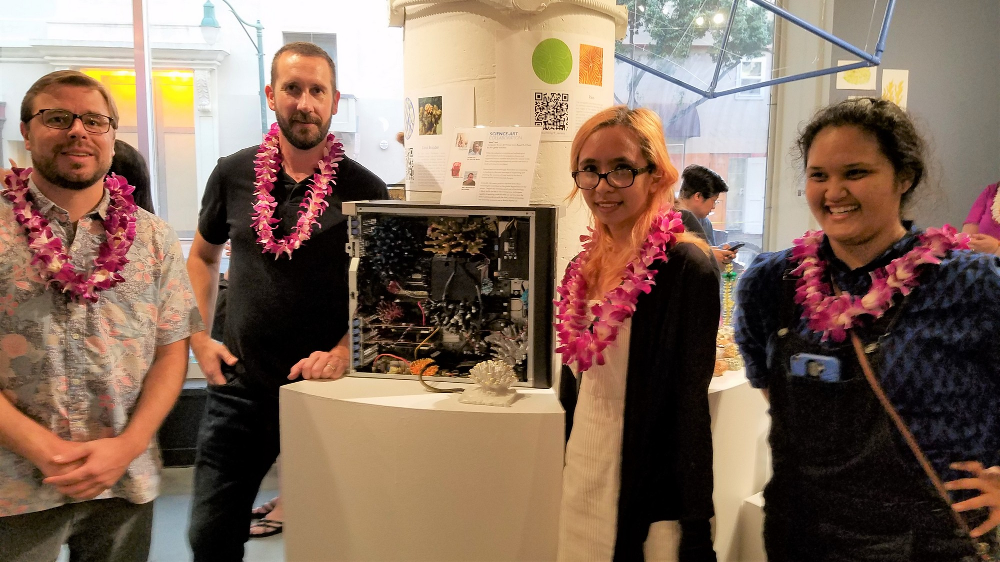 John Burns, Jon Goebel, Jade Kauwe, and Kawelina Cruz stand next to their 3D artwork of corals.