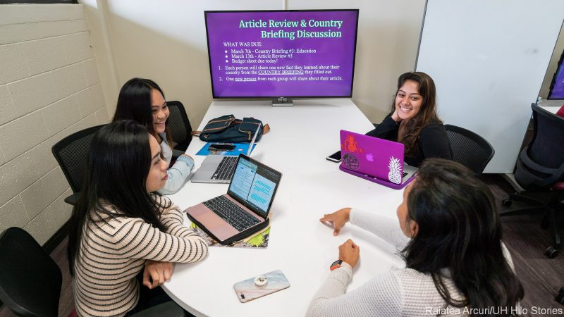 """Group of students in discussion at a table with assignment on screen """"Article Review & Country Briefing Discussion."""""""