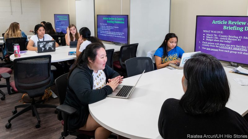 """Students in class seated at three tables with screen discussing assignment. Assignment on screen """"Article Review & Country Briefing Discussion."""""""