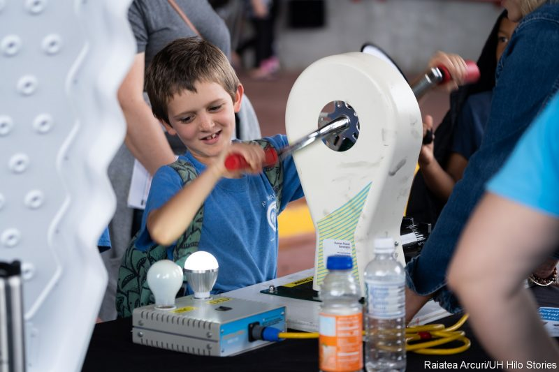Boy generating electricity with hand crank.