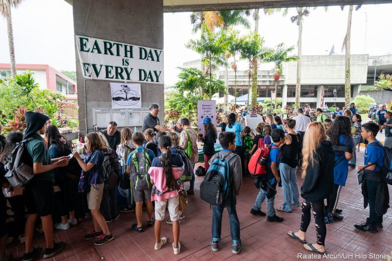 """School children viewing displays. Sign"""" Earth Day is Every Day."""