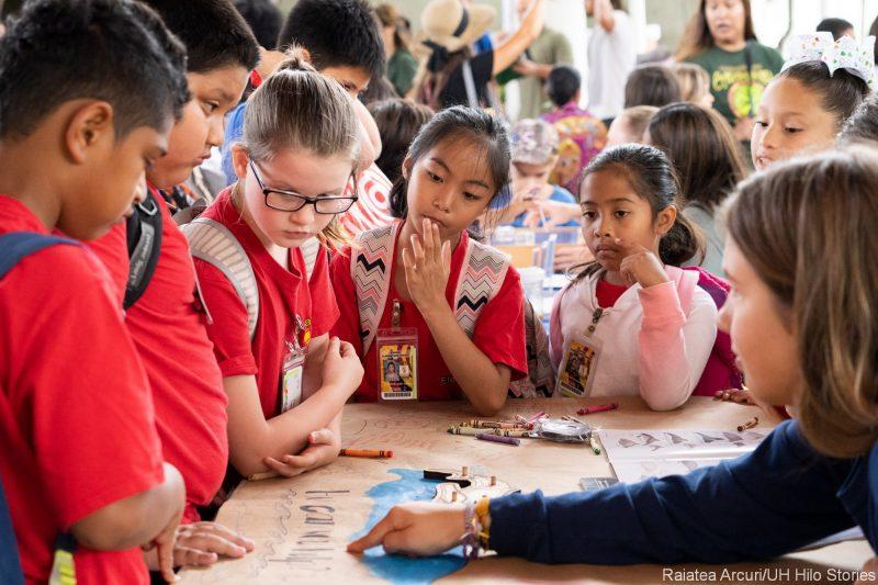 Schoolchildren gather around an informational table.