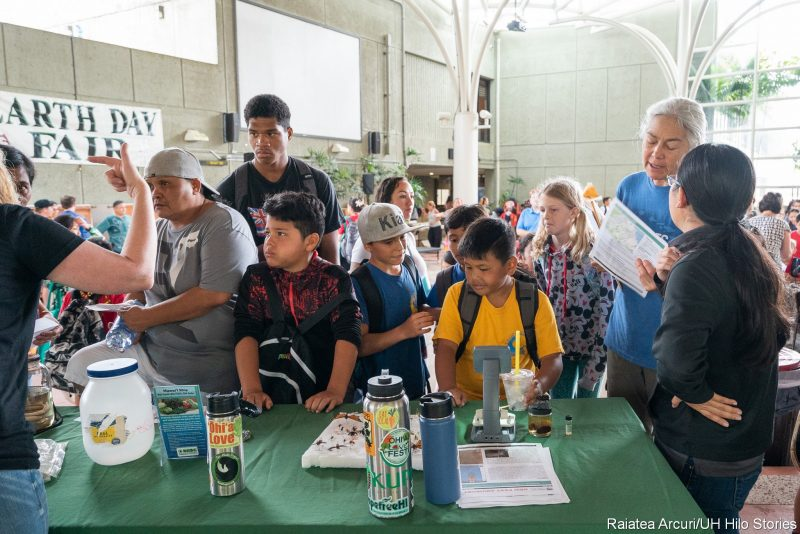 Children viewing objects on table at at a display.