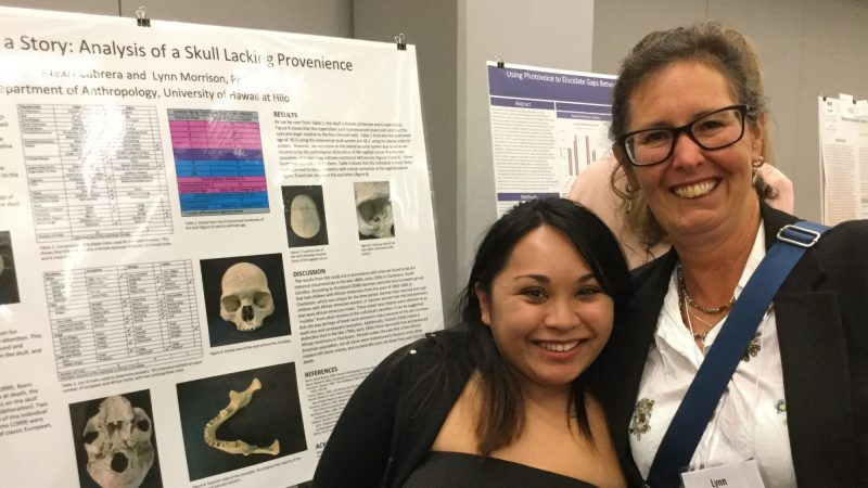 Alexis Cabrera and Lynn Morrison. Poster is in background, title ....Story: Analysis of a Skull Lacking Provenience.