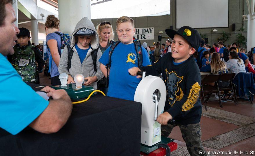 Boy creates electricity with hand crank.