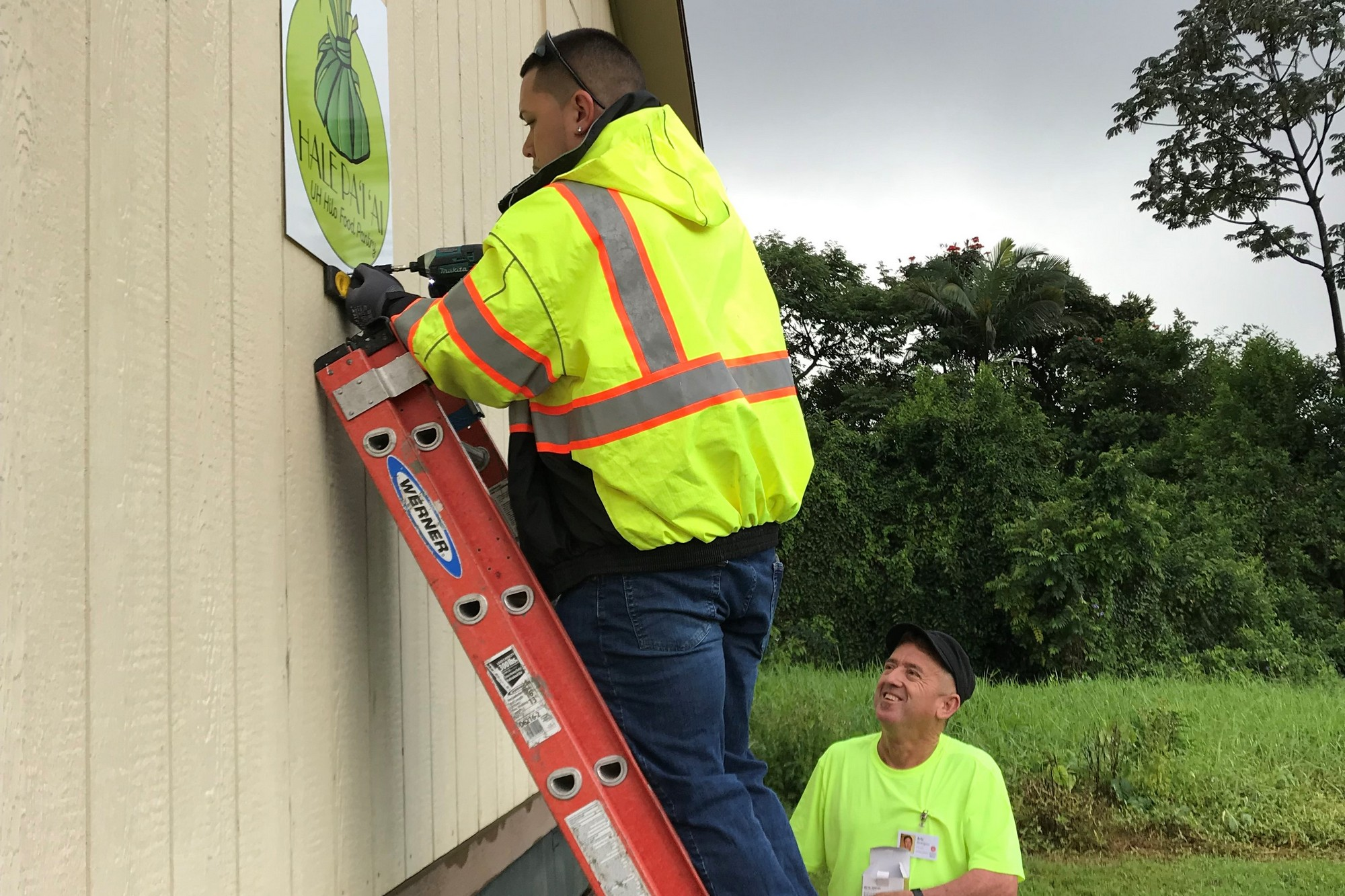 A worker screw a sogn on the side of the building, while another looks on.