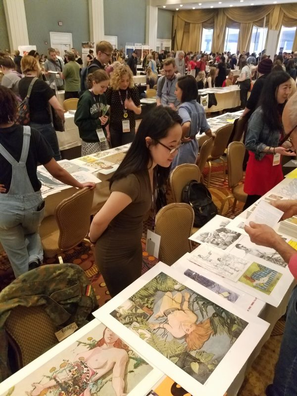 Rachel Kishimoto looks at prints on display table.