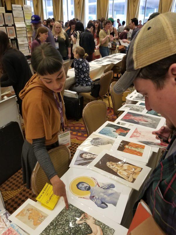 Katya Huchinson looks at prints on display table.