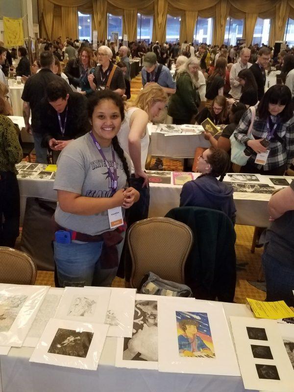 Kawe Cruz poses for photo beside display table.