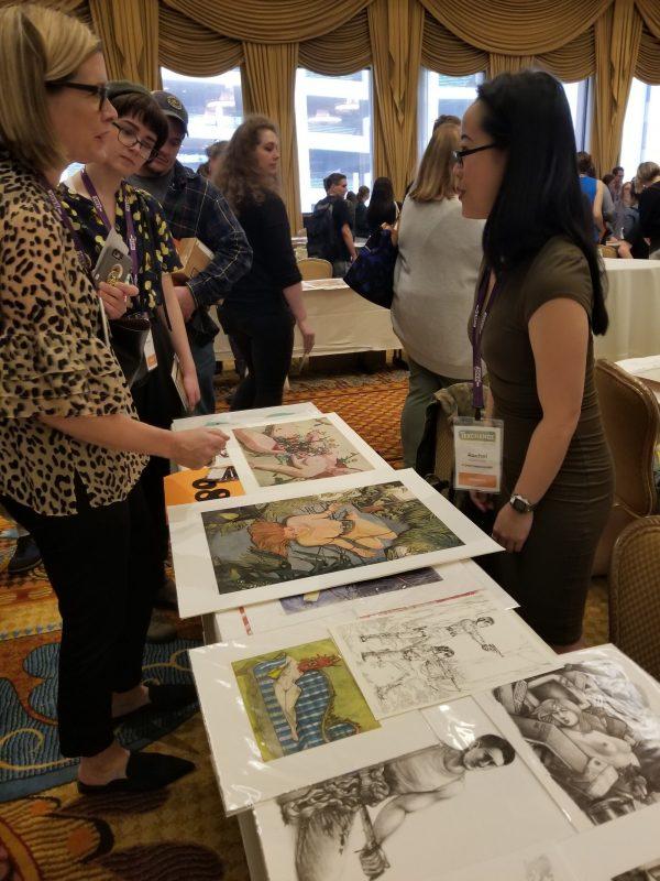 Rachel Kishimoto talks to visitor at display table.