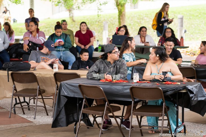 Students at tables on plaza.