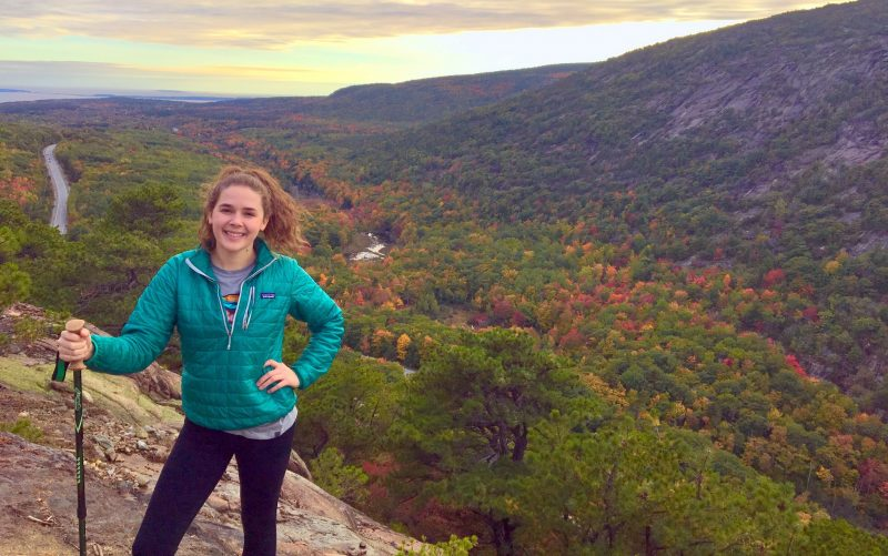 Devyn in Acadia National Park, panoramic view behind her, fall colors in the trees
