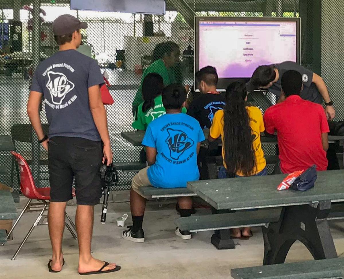Students gather around monitor screen.