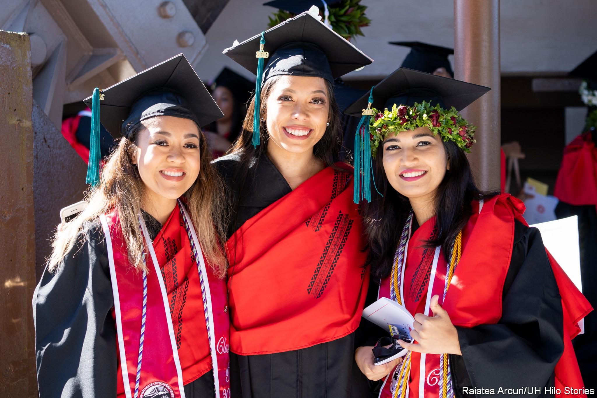 Three women graduates in regalia before ceremonies.