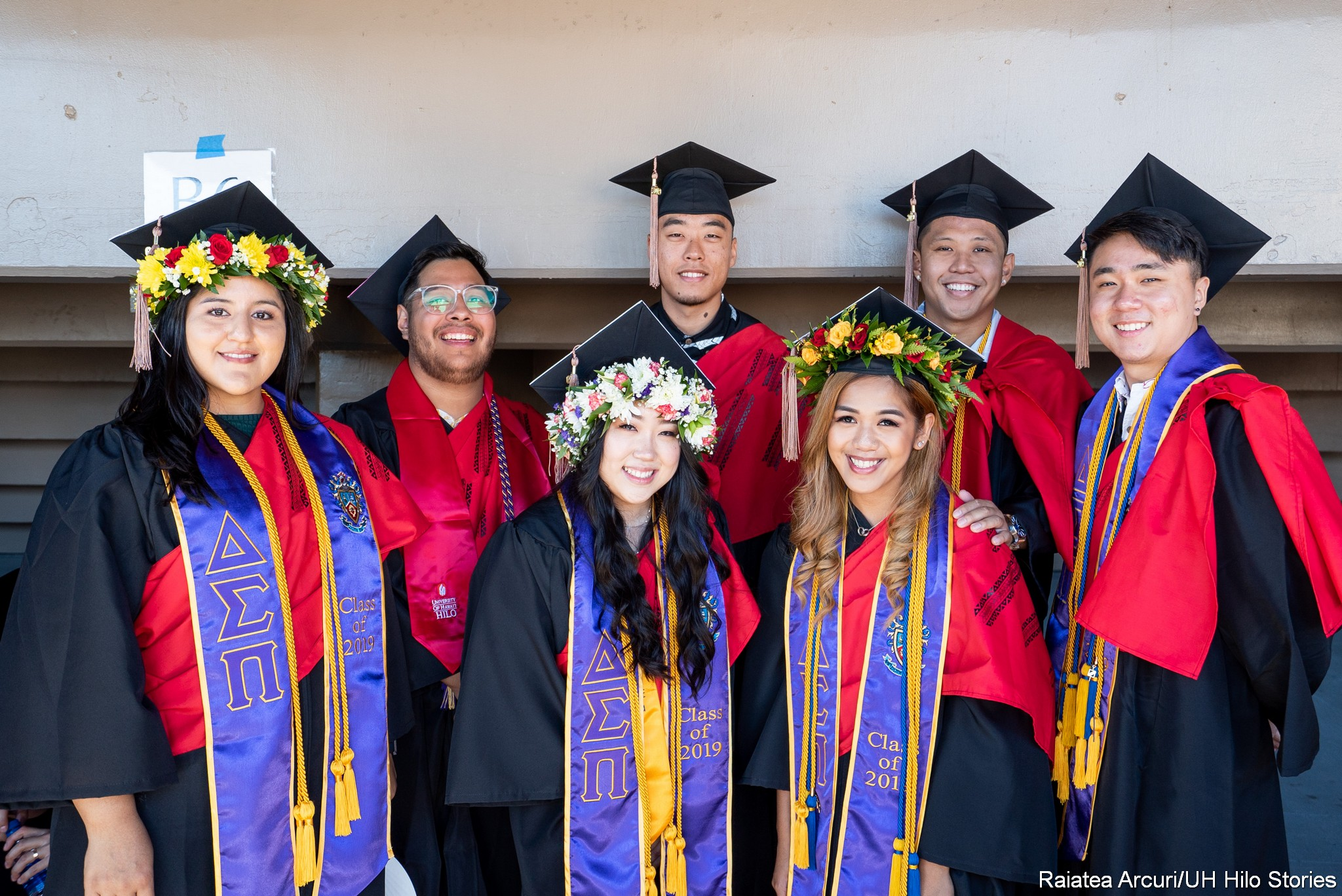 Group of graduates before ceremonies pose for group photo.