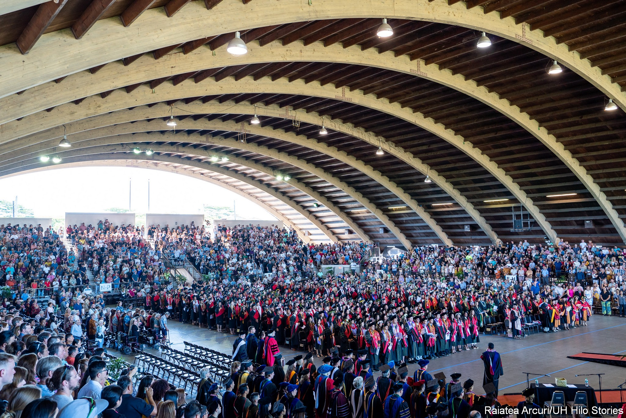 Wide view of venue with large arching ceiling and graduates standing at their seats.