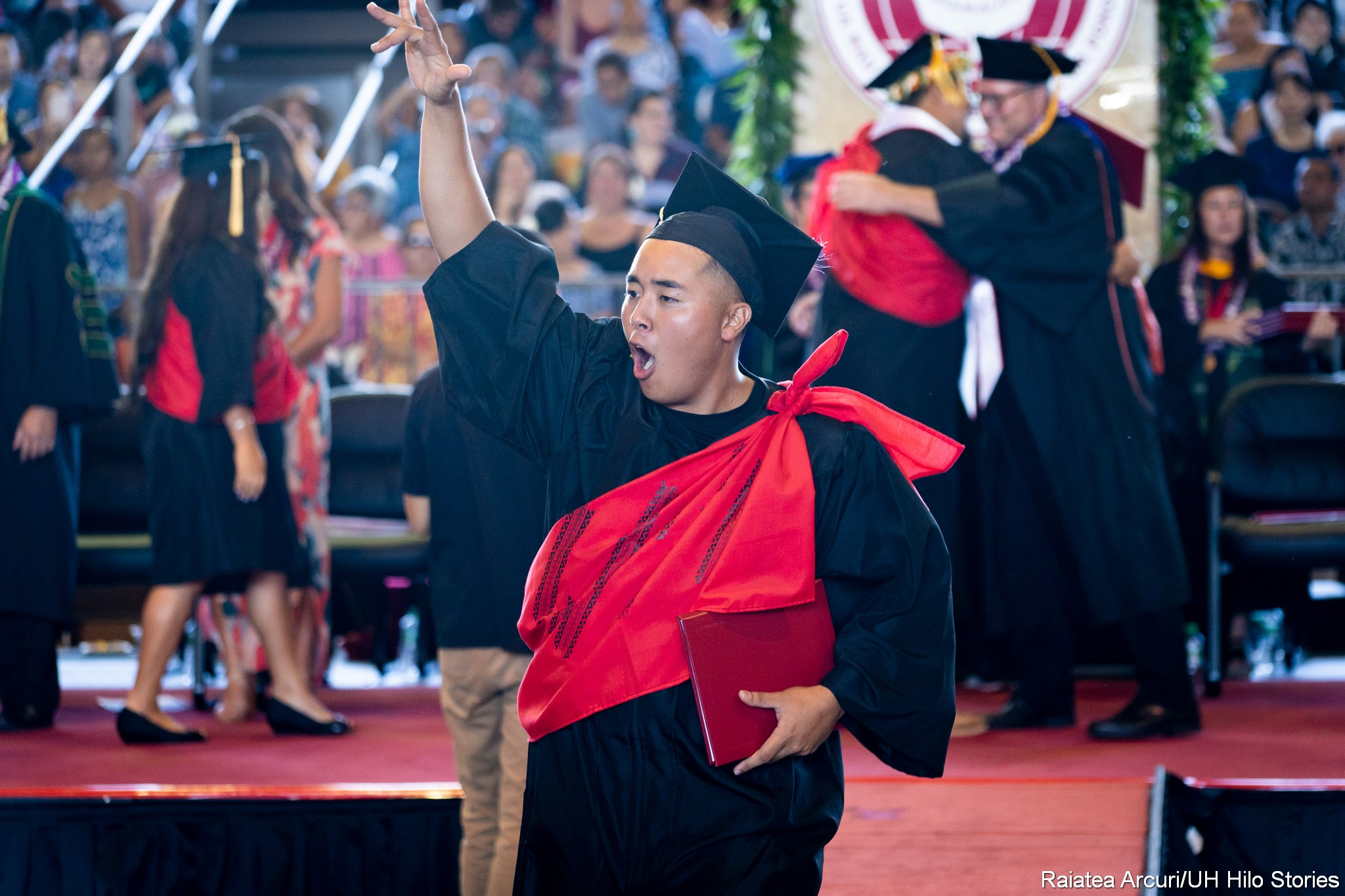 Graduate leaving dais holding diploma overhead.