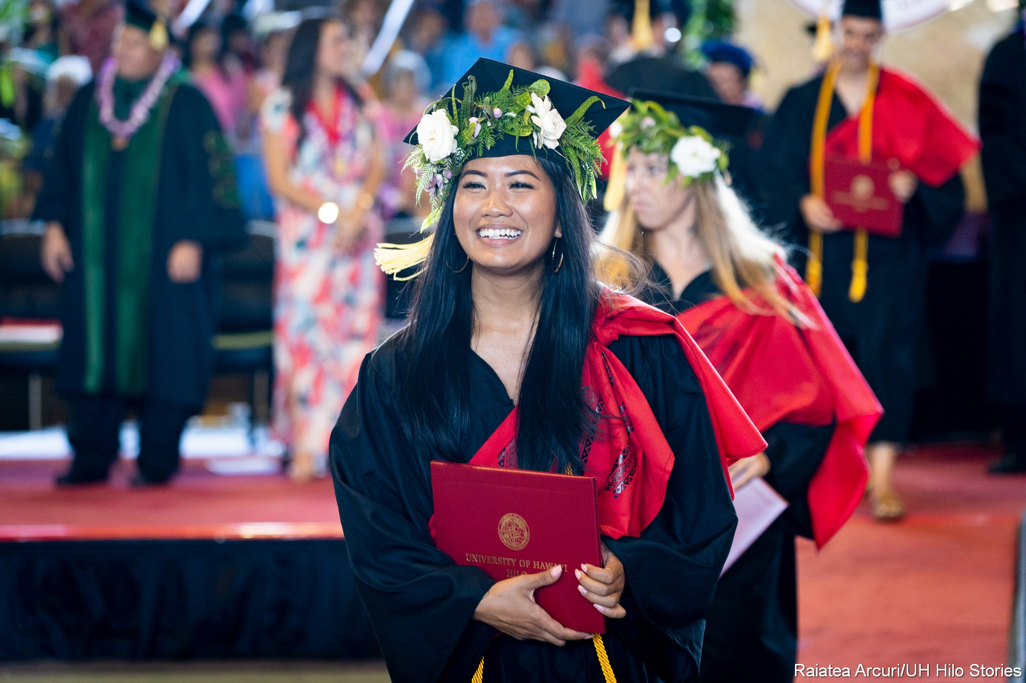Graduate with head lei leaving dais with diploma in hand.