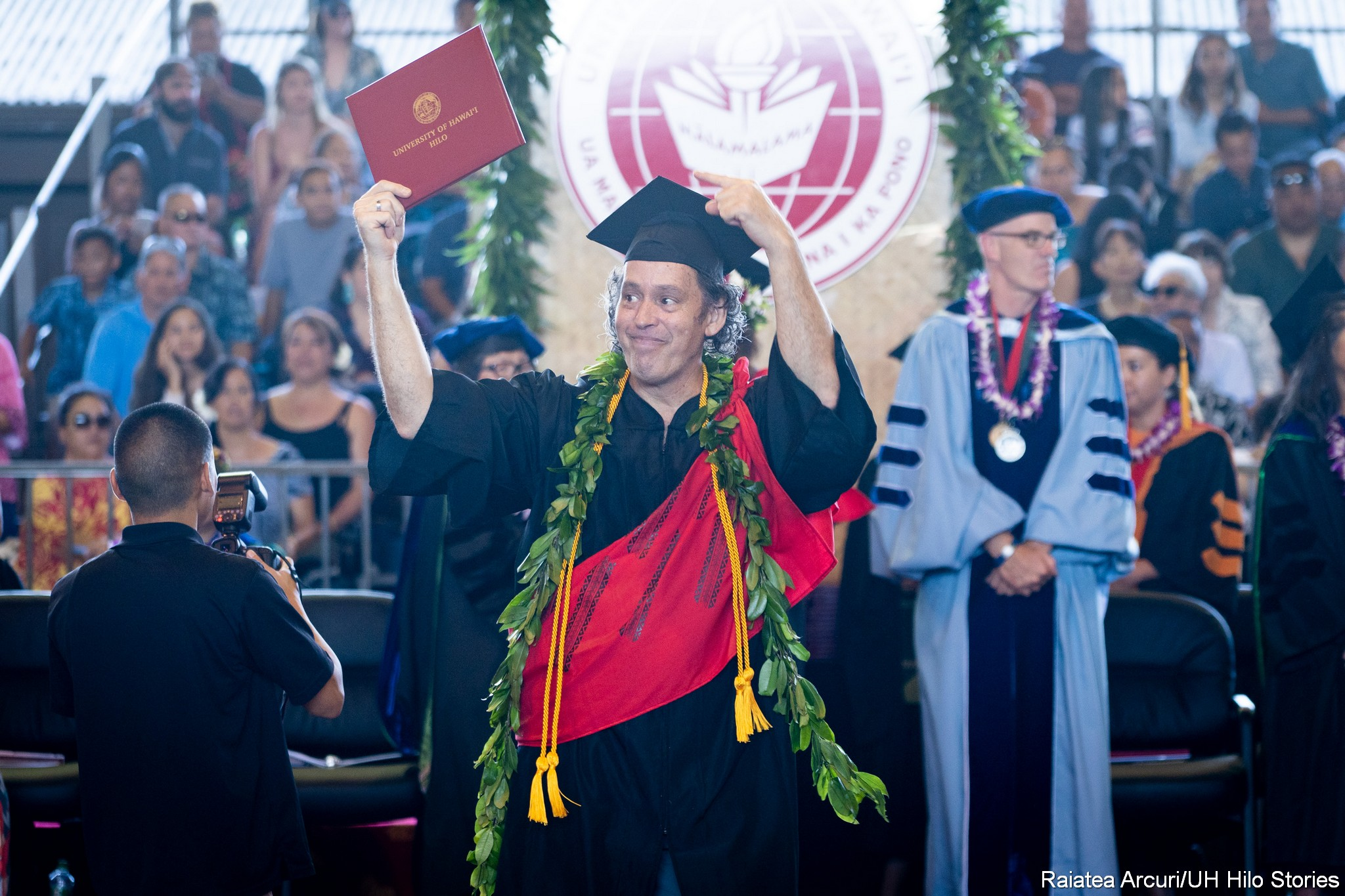 Male graduate, diploma held overhead, leaving dais.
