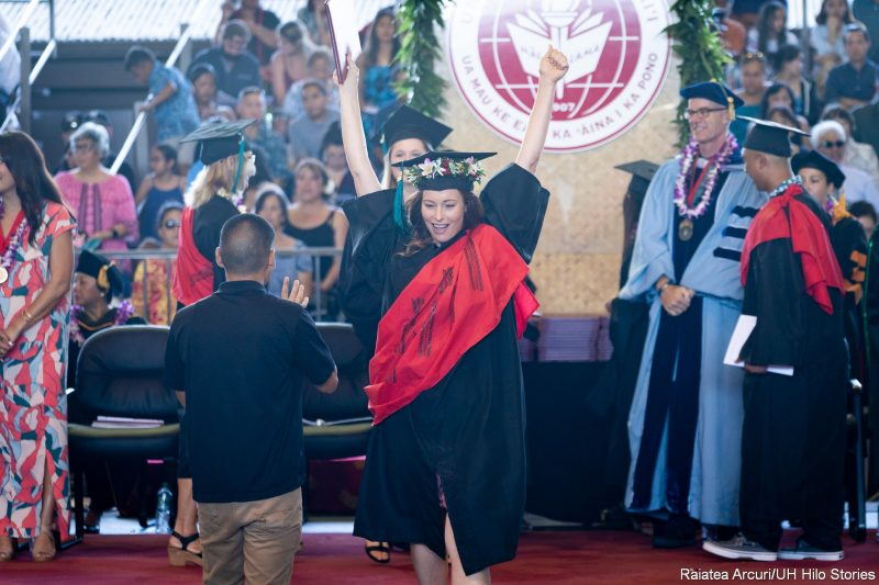 Female graduate leaving dais with diploma held high over head.