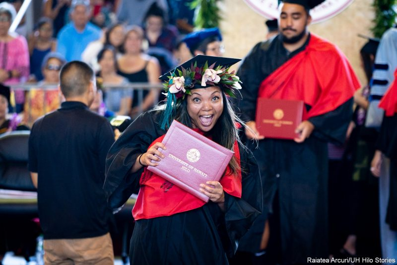 Graduate gives big exuberant smile while leaving dais with diploma.