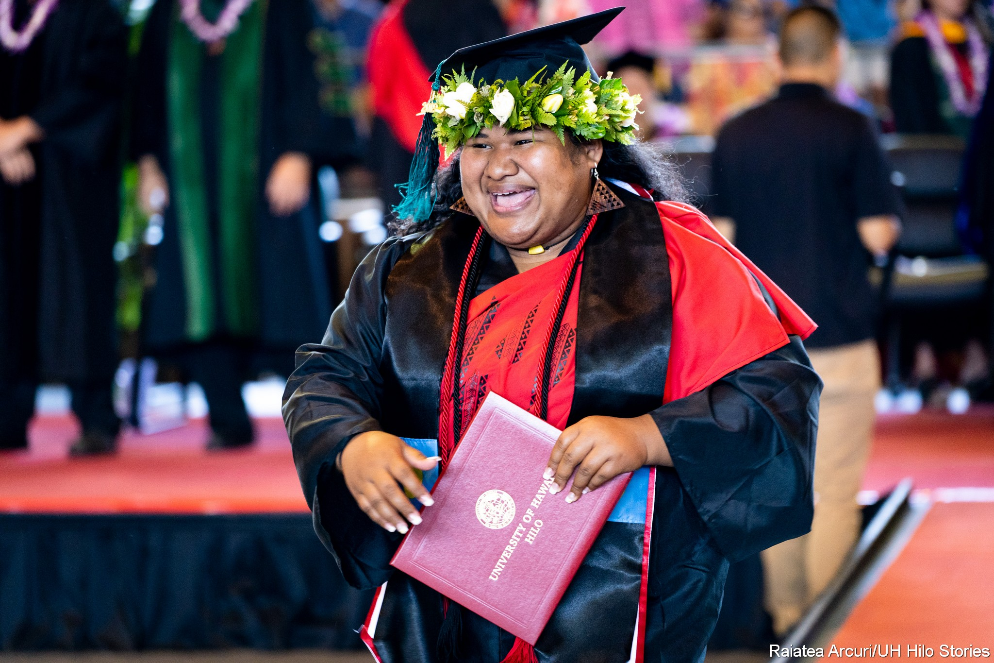 Big smile on female graduate as she leaves dais with diploma.