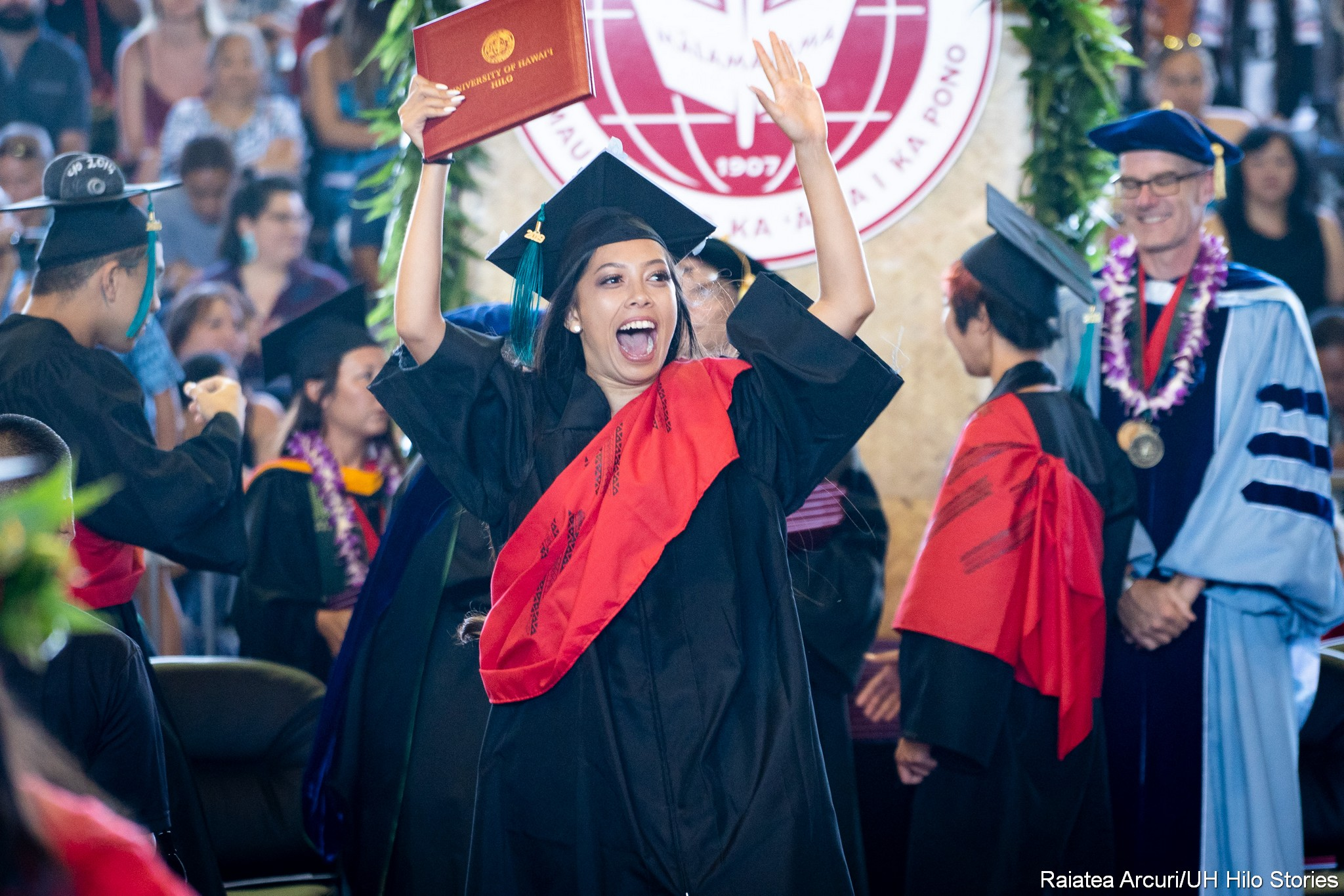 Female graduate with big smile and hands overhead leaving dais with diploma.