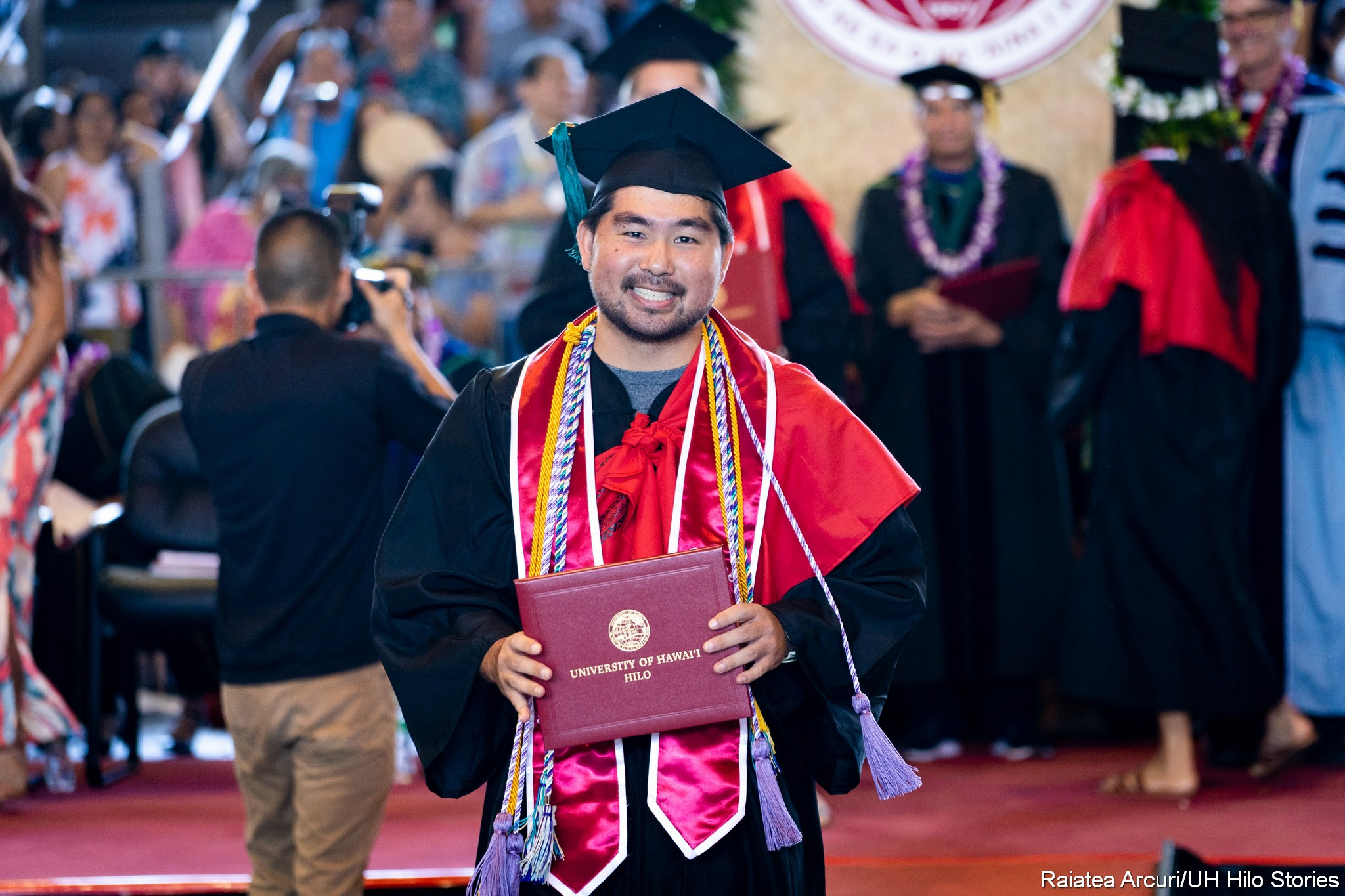 Male graduate with red sash, gold cord, purple cord, leaving dais with diploma.