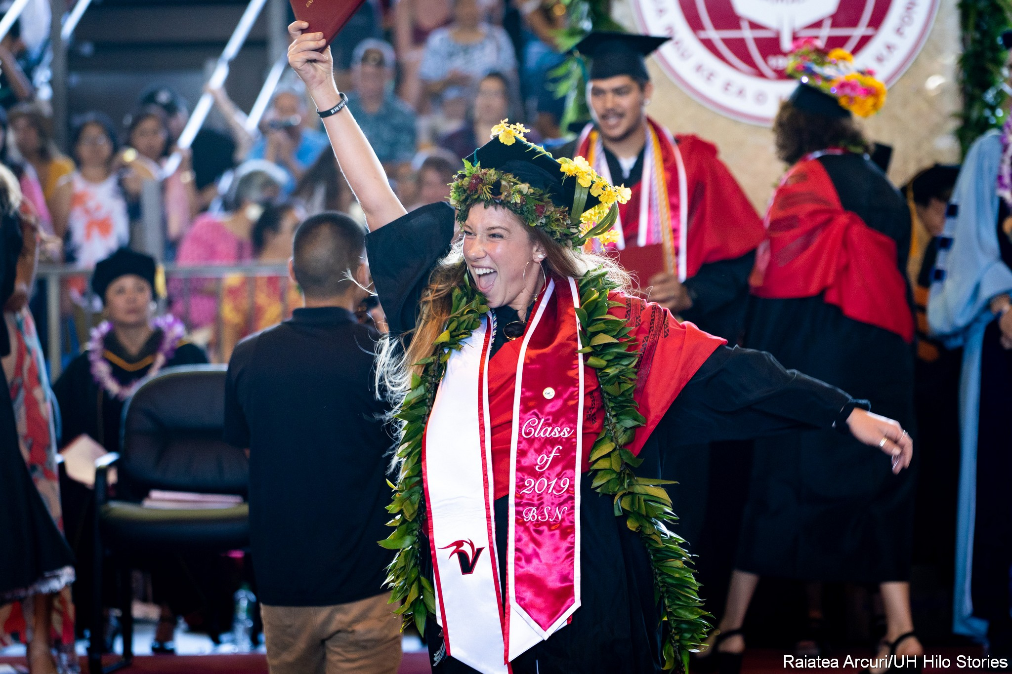 Female graduate leaving dais with diploma held high over head, showing audience members.