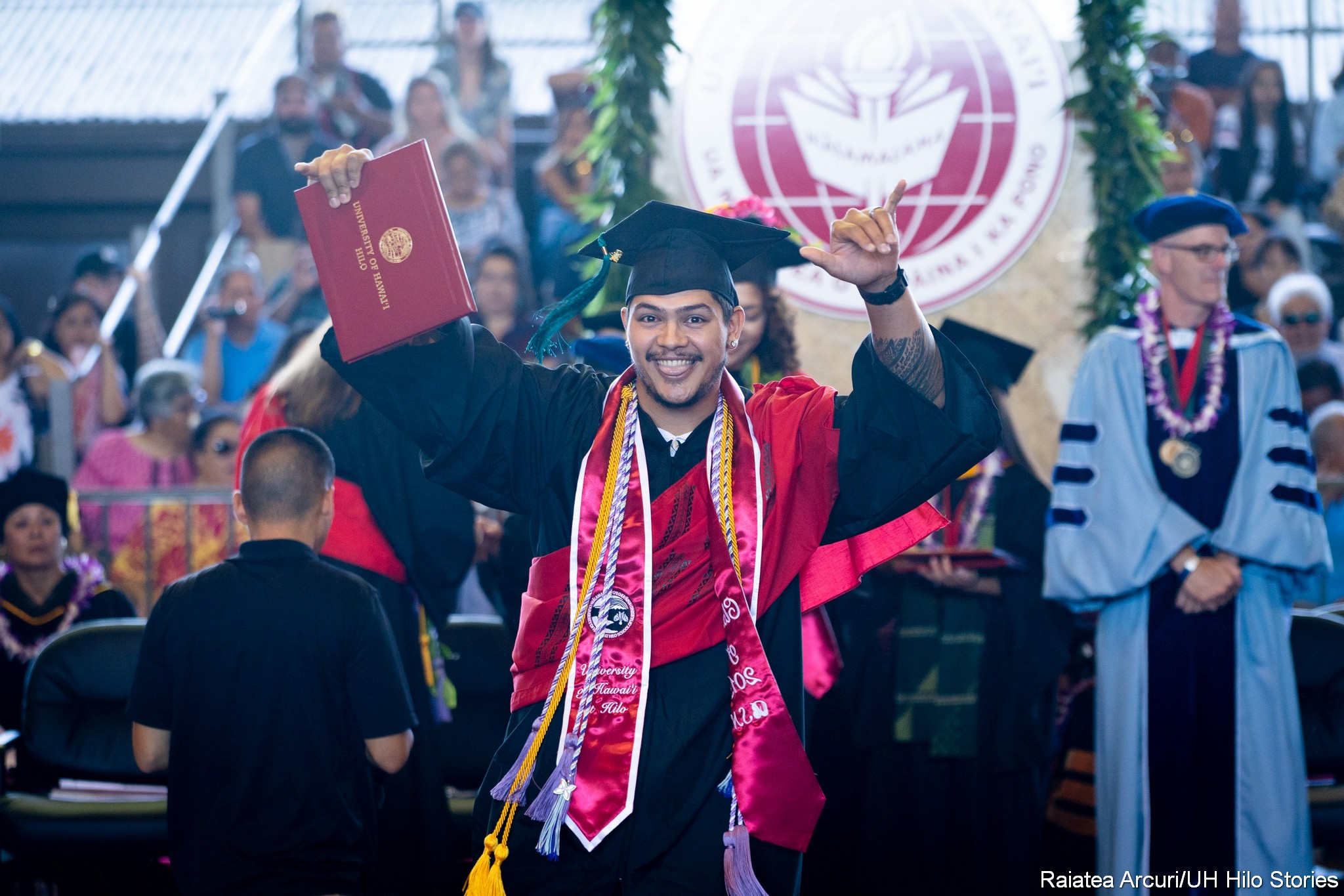Male graduate leaving dais with diploma held high in right hand.