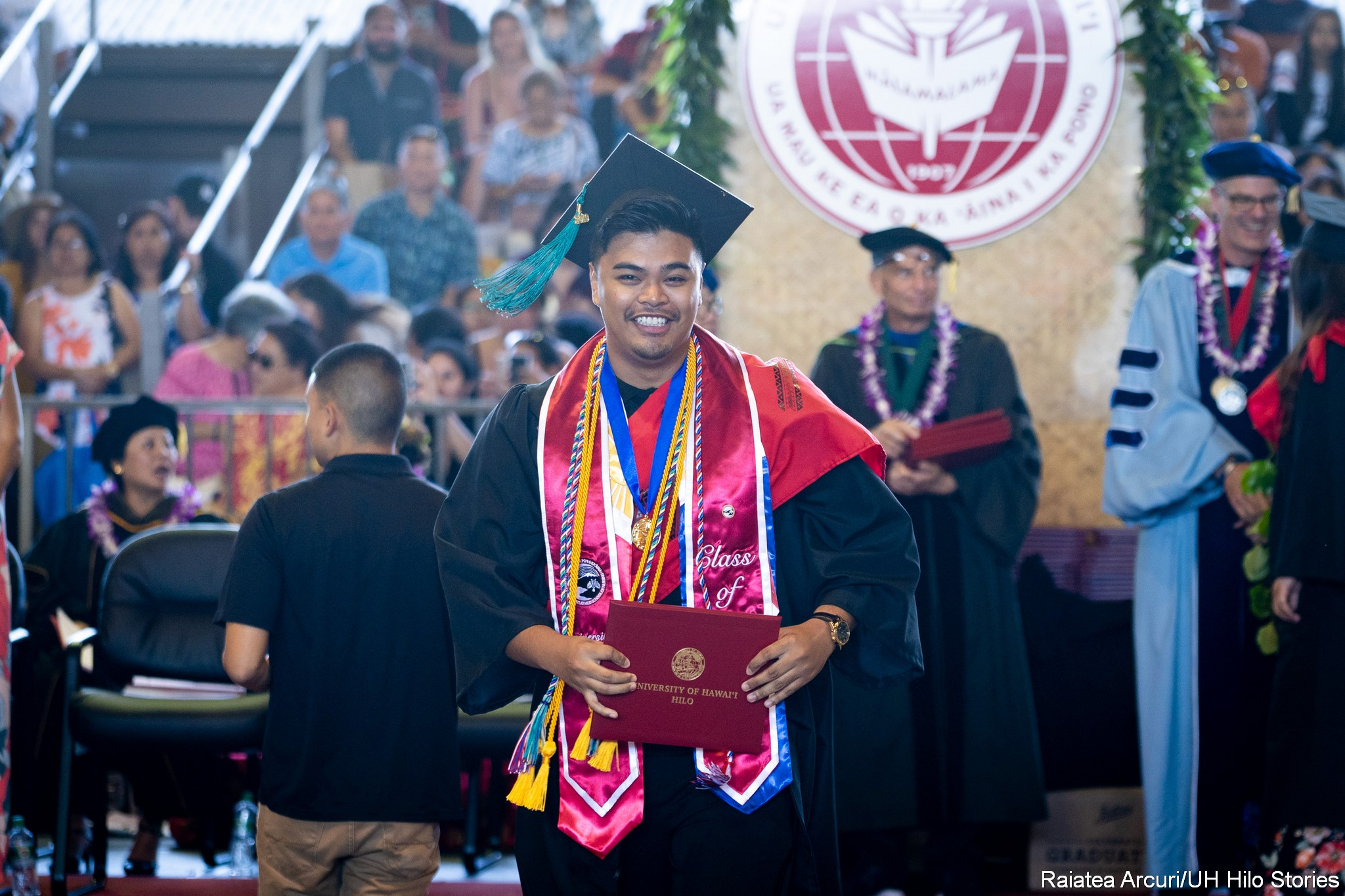 Male graduate with red sash, gold and blue cords, leaving dais with diploma.