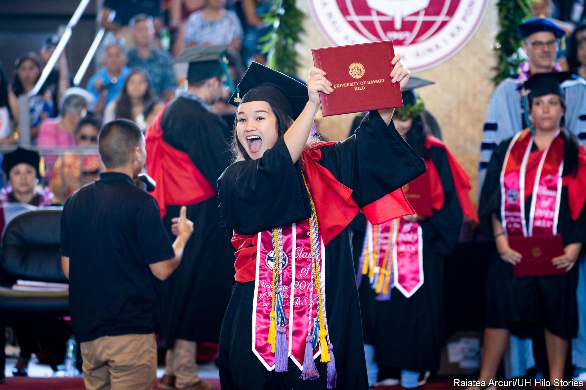 Female graduate jubilantly leaving dais holding up diploma.