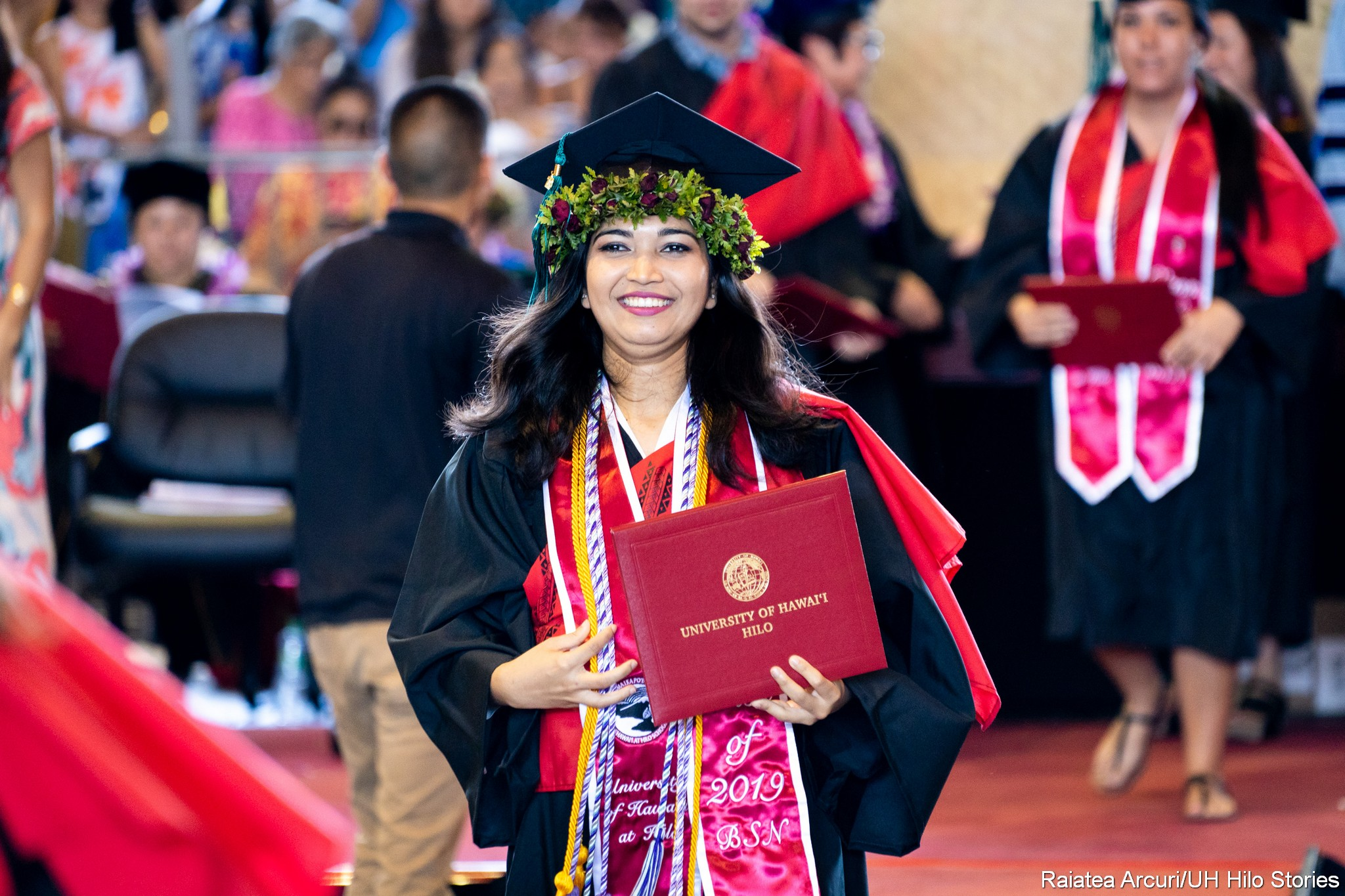 Female graduate with multiple cords and head lei on cap leaving dais with diploma.
