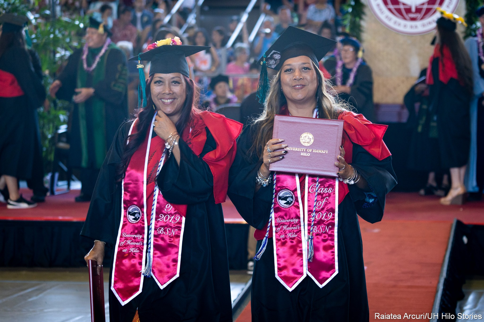 Two female graduates leaving dais with diploma.
