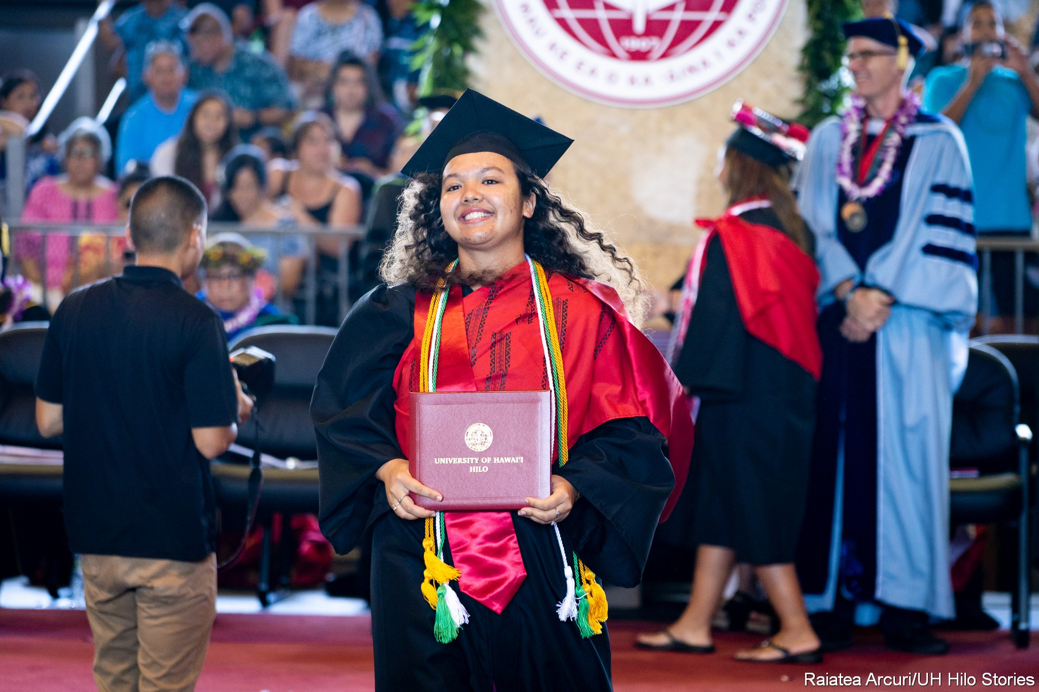 Female graduate with wavy hair leaving dais with diploma.