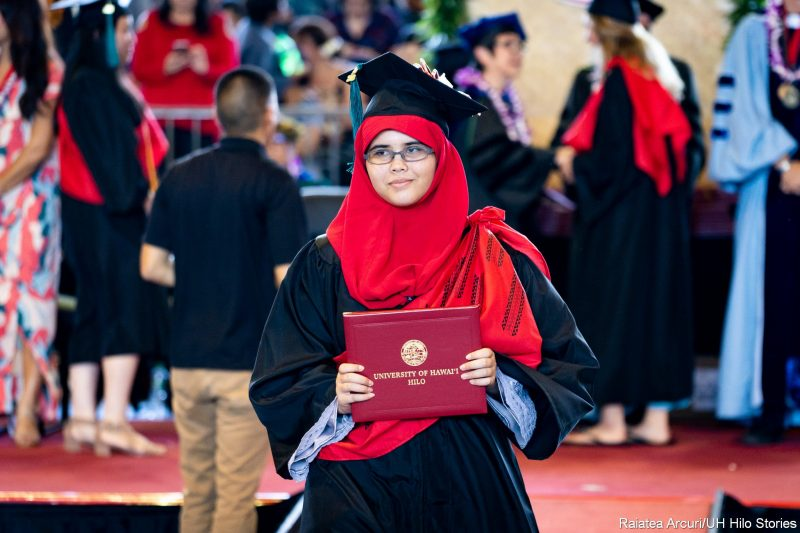 Female graduate in red hijab leaving dais with diploma.